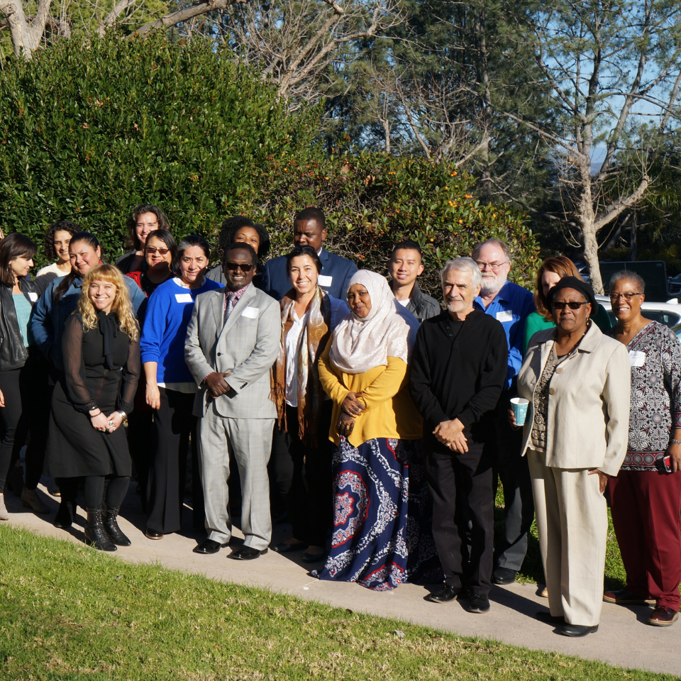 A large group of diverse individuals posing together in an outdoor setting