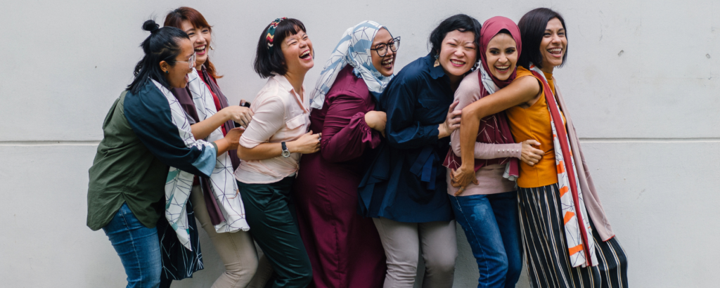 A diverse group of seven women laughing in a line